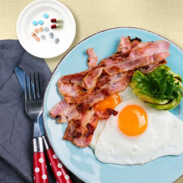 plate of eggs and bacon next to dish of prescription medicines